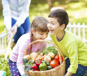 Children smiling at vegetable garden with busket full of vegetables in front of them